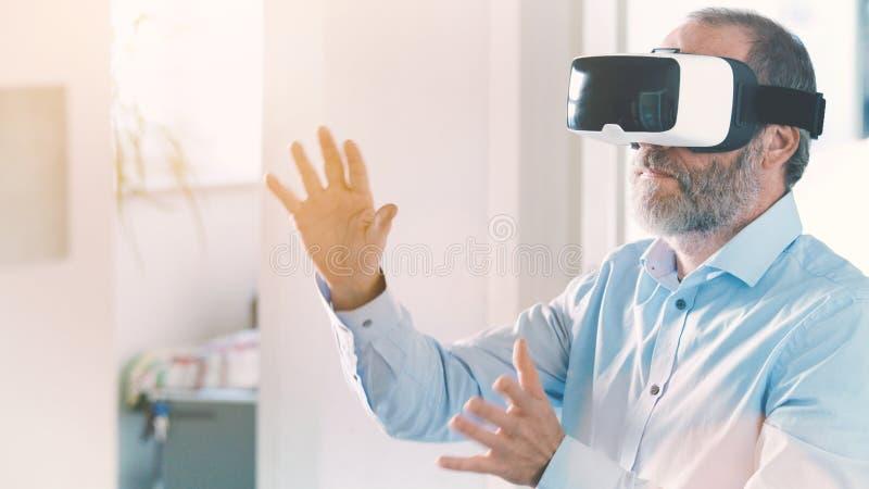 Ώριμο επιχειρησιακό άτομο που φορά την εικονική πραγματικότητα googles/τα γυαλιά VR στοκ φωτογραφίες