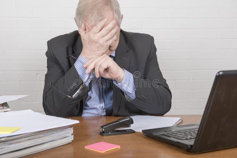 Ώριμο επιχειρησιακό άτομο σε ένα γραφείο που θέτει να φανεί κουρασμένος στοκ φωτογραφίες