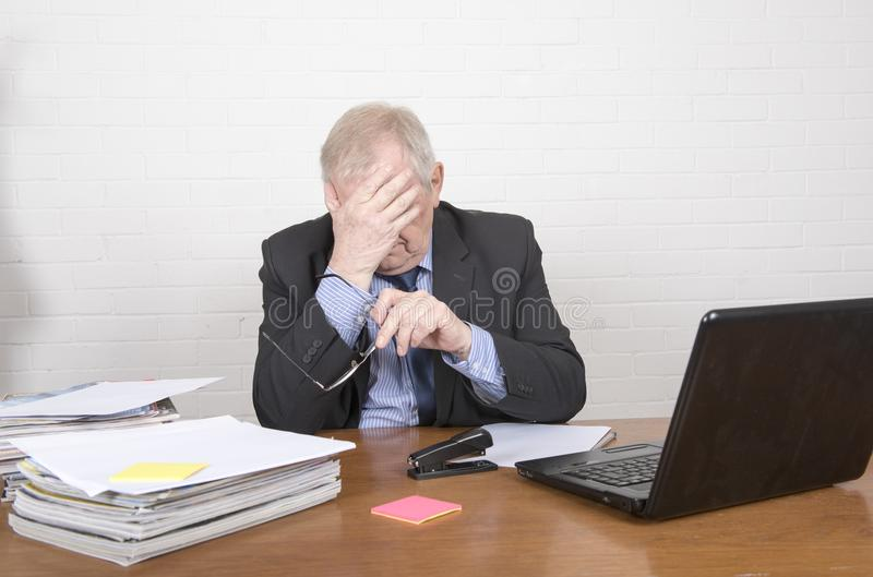 Ώριμο επιχειρησιακό άτομο σε ένα γραφείο που θέτει να φανεί κουρασμένος στοκ εικόνα με δικαίωμα ελεύθερης χρήσης