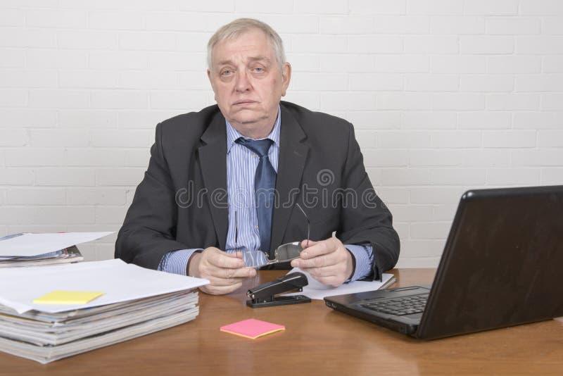 Ώριμο επιχειρησιακό άτομο σε ένα γραφείο που θέτει να φανεί κουρασμένος στοκ εικόνες με δικαίωμα ελεύθερης χρήσης