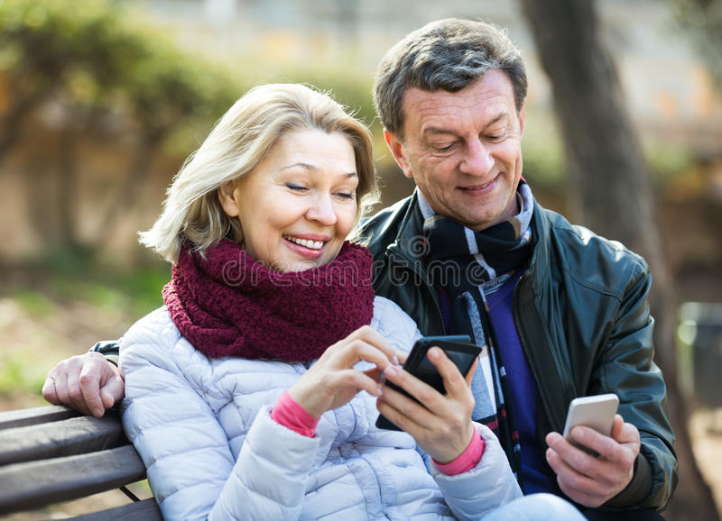 Ώριμο ζεύγος με τα smartphones υπαίθρια στοκ φωτογραφίες