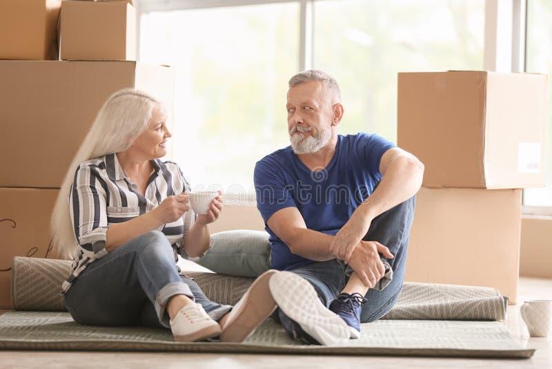 Ώριμο ζεύγος με τις περιουσίες που κάθεται στον τάπητα και το τσάι κατανάλωσης στο εσωτερικό Κίνηση στο καινούργιο σπίτι στοκ φωτογραφίες