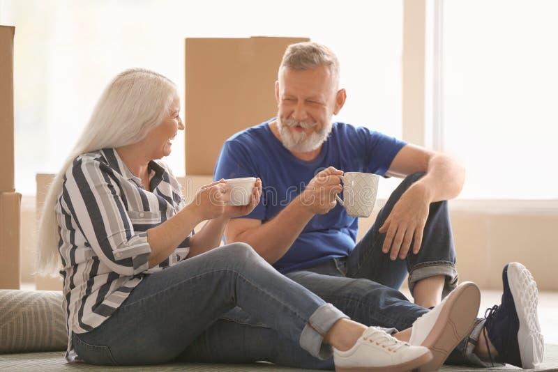 Ώριμο ζεύγος με τις περιουσίες που κάθεται στον τάπητα και το τσάι κατανάλωσης στο εσωτερικό Κίνηση στο καινούργιο σπίτι στοκ φωτογραφίες με δικαίωμα ελεύθερης χρήσης