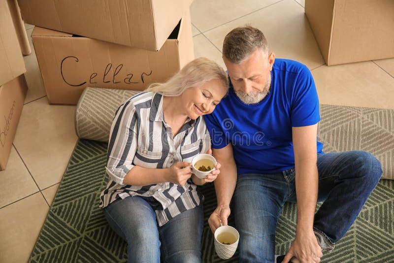 Ώριμο ζεύγος με τις περιουσίες που κάθεται στον τάπητα και το τσάι κατανάλωσης στο εσωτερικό Κίνηση στο καινούργιο σπίτι στοκ φωτογραφία
