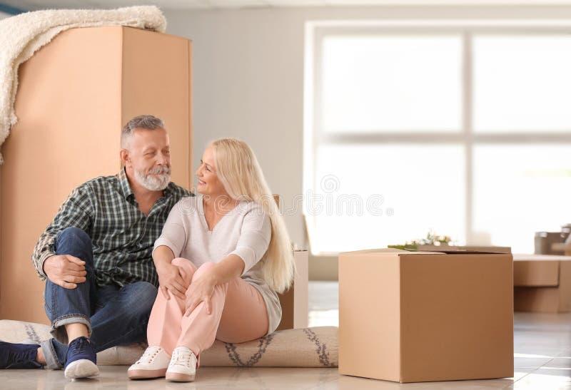 Ώριμο ζεύγος με τις περιουσίες που κάθεται στον τάπητα στο εσωτερικό Κίνηση στο καινούργιο σπίτι στοκ φωτογραφίες με δικαίωμα ελεύθερης χρήσης