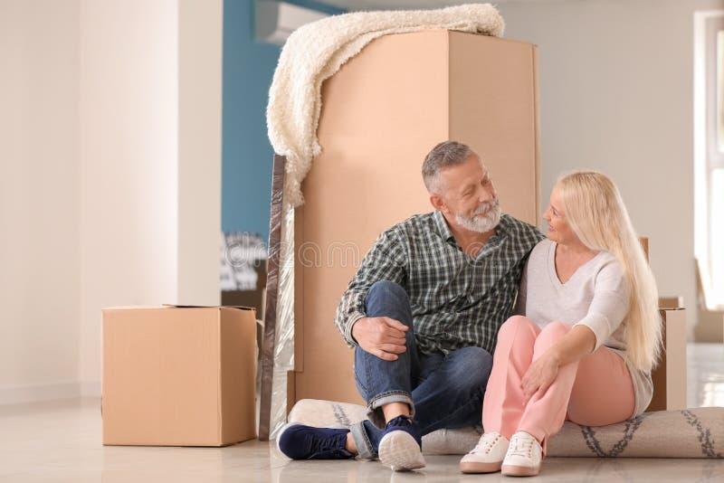 Ώριμο ζεύγος με τις περιουσίες που κάθεται στον τάπητα στο εσωτερικό Κίνηση στο καινούργιο σπίτι στοκ εικόνα