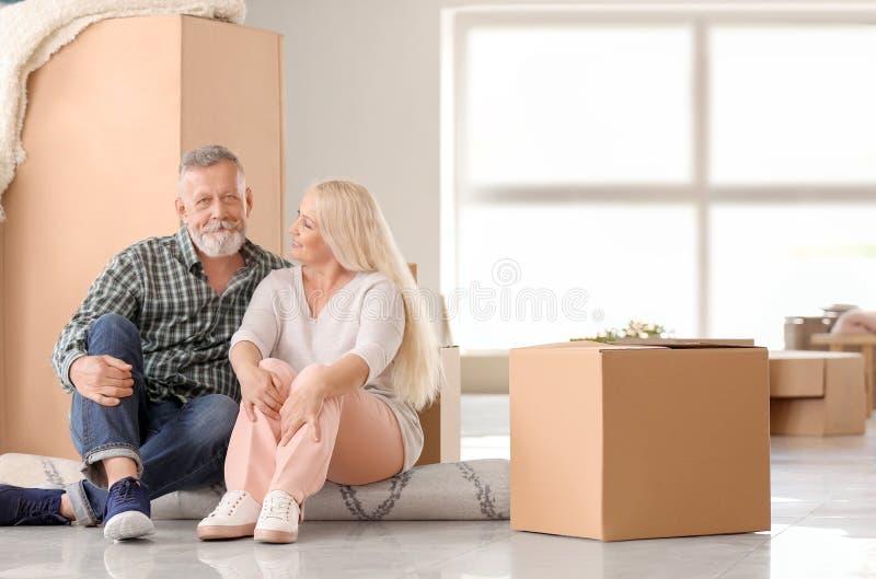 Ώριμο ζεύγος με τις περιουσίες που κάθεται στον τάπητα στο εσωτερικό Κίνηση στο καινούργιο σπίτι στοκ φωτογραφίες