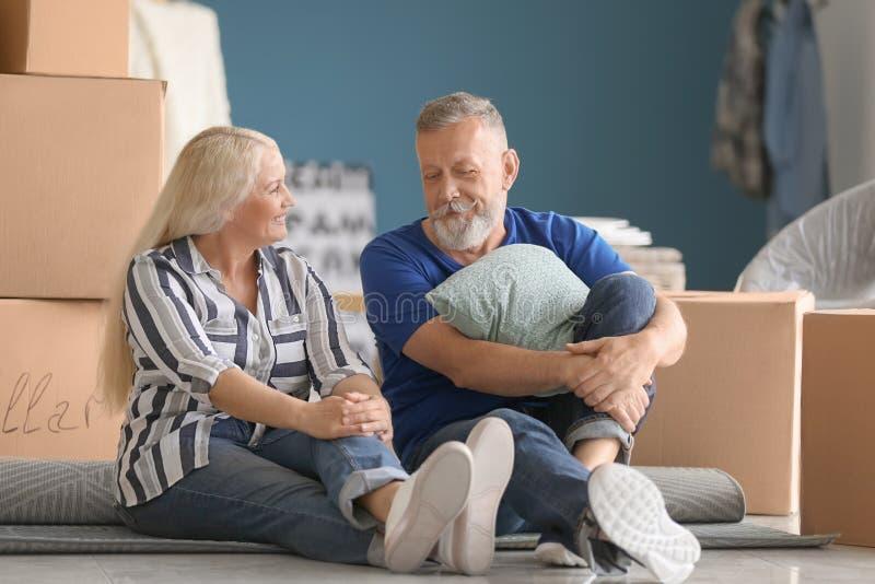 Ώριμο ζεύγος με τις περιουσίες που κάθεται στο πάτωμα στο εσωτερικό Κίνηση στο καινούργιο σπίτι στοκ εικόνες