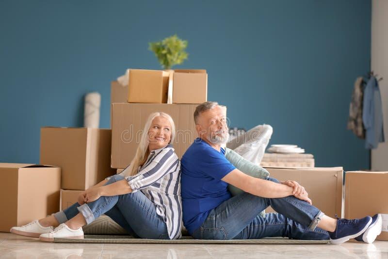 Ώριμο ζεύγος με τις περιουσίες που κάθεται στο πάτωμα στο εσωτερικό Κίνηση στο καινούργιο σπίτι στοκ φωτογραφίες