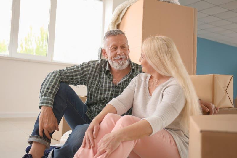 Ώριμο ζεύγος με τις περιουσίες που κάθεται στο πάτωμα στο εσωτερικό Κίνηση στο καινούργιο σπίτι στοκ εικόνες με δικαίωμα ελεύθερης χρήσης