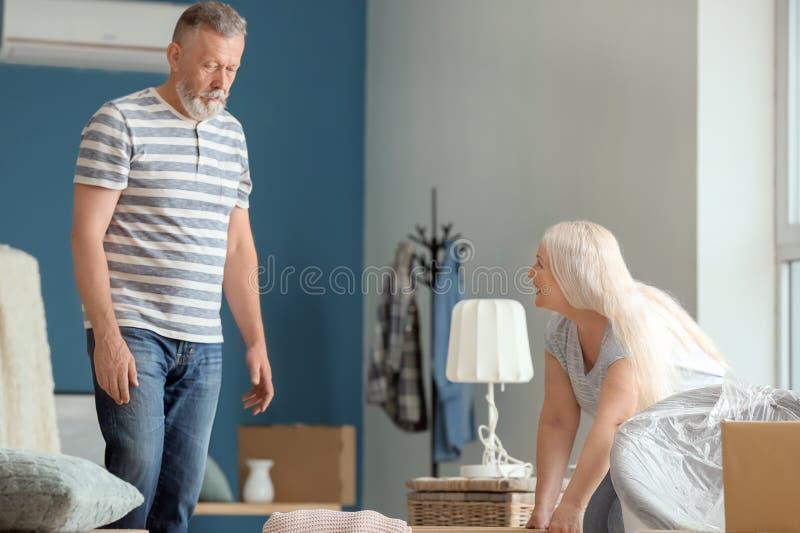 Ώριμο ζεύγος με τις περιουσίες στο εσωτερικό Κίνηση στο καινούργιο σπίτι στοκ φωτογραφία με δικαίωμα ελεύθερης χρήσης