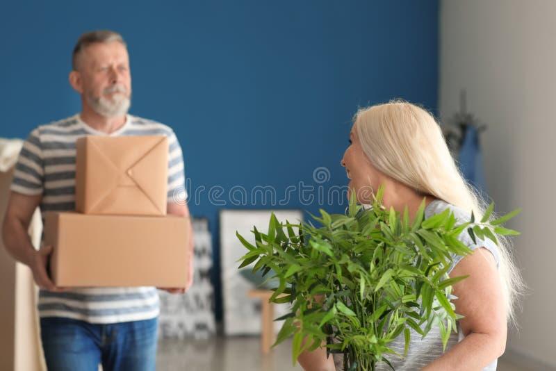 Ώριμο ζεύγος με τις περιουσίες στο εσωτερικό Κίνηση στο καινούργιο σπίτι στοκ φωτογραφίες