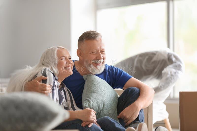Ώριμο ζεύγος με τις περιουσίες στο εσωτερικό Κίνηση στο καινούργιο σπίτι στοκ εικόνες με δικαίωμα ελεύθερης χρήσης