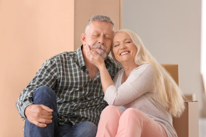 Ώριμο ζεύγος με τις περιουσίες στο εσωτερικό Κίνηση στο καινούργιο σπίτι στοκ φωτογραφία