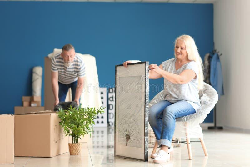 Ώριμο ζεύγος με τις περιουσίες στο εσωτερικό Κίνηση στο καινούργιο σπίτι στοκ φωτογραφίες με δικαίωμα ελεύθερης χρήσης
