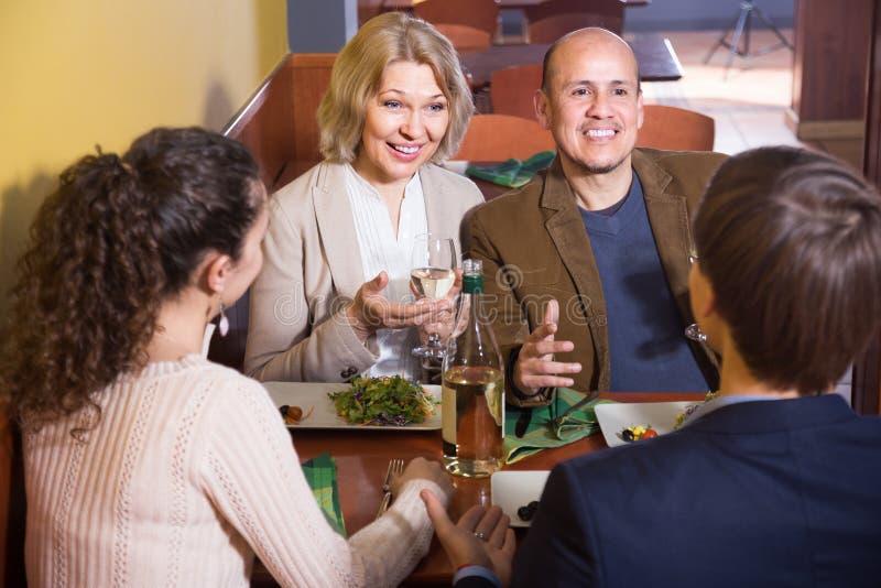 Ώριμο ζεύγος με τους φίλους που έχουν το γεύμα και το κρασί στο εστιατόριο στοκ εικόνες