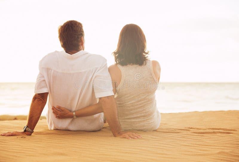 Ώριμο ζεύγος που απολαμβάνει το ηλιοβασίλεμα στην παραλία στοκ εικόνα