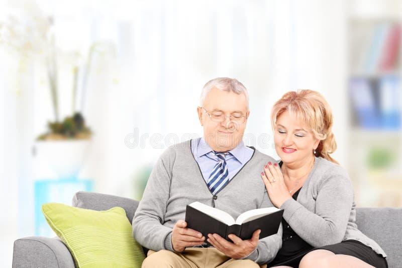 Ώριμο ζεύγος που διαβάζει ένα βιβλίο που κάθεται στον καναπέ στοκ εικόνα με δικαίωμα ελεύθερης χρήσης