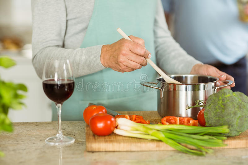 Ώριμο ζεύγος που κάνει το γεύμα μαζί που έχει το κόκκινο κρασί στοκ εικόνες