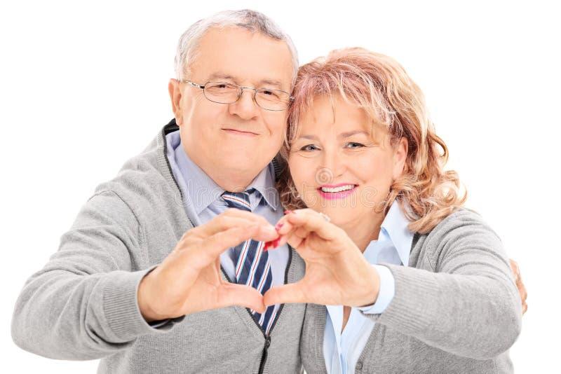 Ώριμο ζεύγος που κατασκευάζει την καρδιά με τα χέρια τους στοκ φωτογραφία