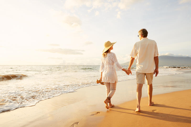 Ώριμο ζεύγος που περπατά στην παραλία στο ηλιοβασίλεμα στοκ εικόνα