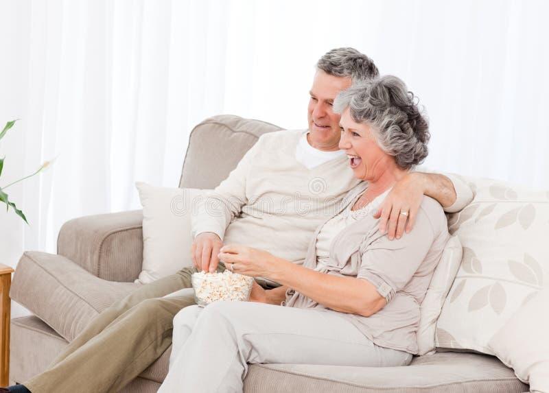 Ώριμο ζεύγος που προσέχει τη TV στο καθιστικό τους στοκ εικόνες