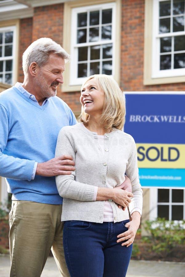Ώριμο ζεύγος που στέκεται έξω από το νέο σπίτι με το πωλημένο σημάδι στοκ εικόνες