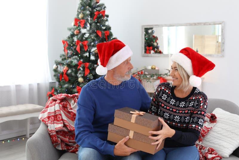 Ώριμο ζεύγος στα καπέλα Santa με τα κιβώτια δώρων Χριστουγέννων στοκ εικόνες με δικαίωμα ελεύθερης χρήσης