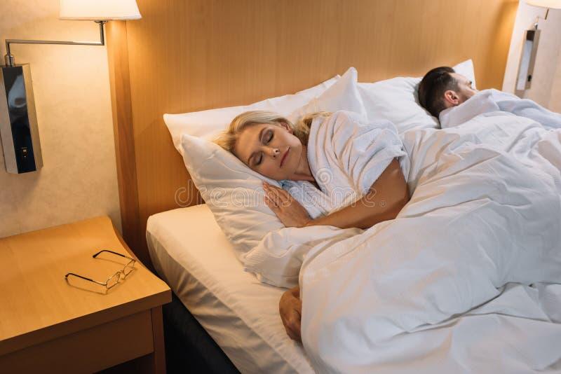 ώριμο ζεύγος στα μπουρνούζια που κοιμούνται στο κρεβάτι και eyeglasses στον πίνακα στο ξενοδοχείο στοκ εικόνες