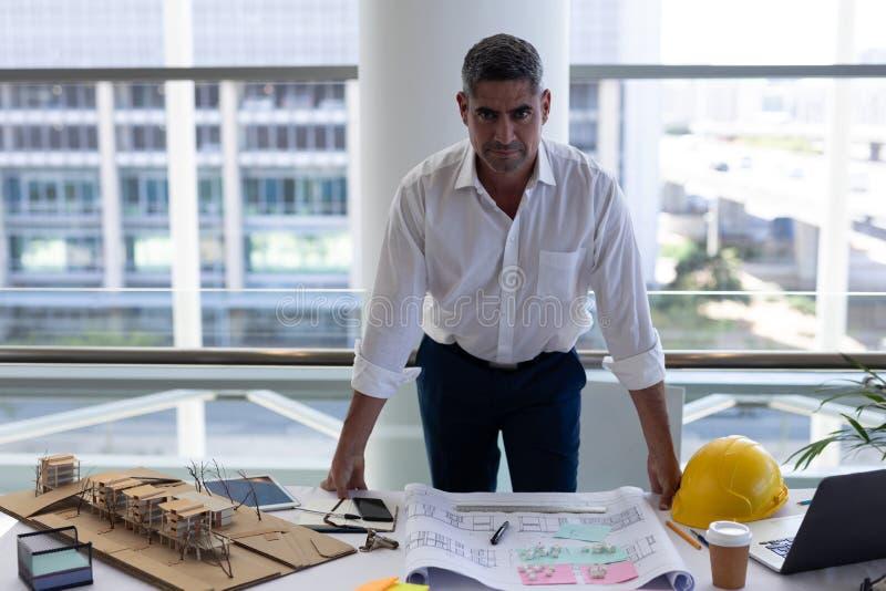 Ώριμο καυκάσιο αρσενικό που εξετάζει τη κάμερα στο γραφείο στοκ εικόνα