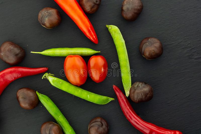 Ώριμο λαχανικών πράσινων μπιζελιών φρέσκο μίγμα κερασιών ντοματών πιπεριών τσίλι λοβών κόκκινο σε μια μαύρη βάση σχεδίου υποβάθρο στοκ εικόνες με δικαίωμα ελεύθερης χρήσης