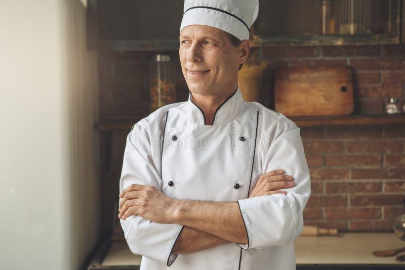 Ώριμο μαγειρεύοντας γεύμα αρχιμαγείρων ατόμων επαγγελματικό στο εσωτερικό στοκ φωτογραφία