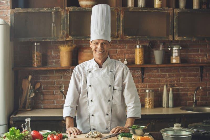 Ώριμο μαγειρεύοντας γεύμα αρχιμαγείρων ατόμων επαγγελματικό στο εσωτερικό στοκ φωτογραφία με δικαίωμα ελεύθερης χρήσης