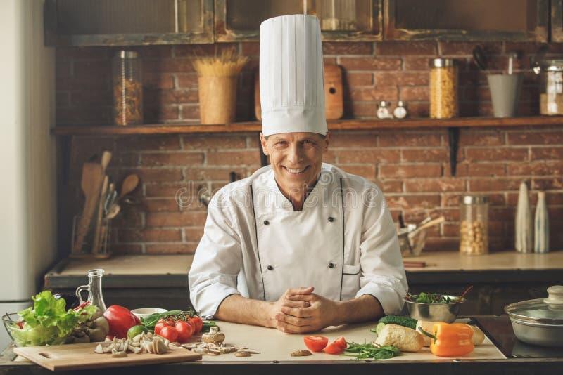 Ώριμο μαγειρεύοντας γεύμα αρχιμαγείρων ατόμων επαγγελματικό στο εσωτερικό στοκ εικόνες