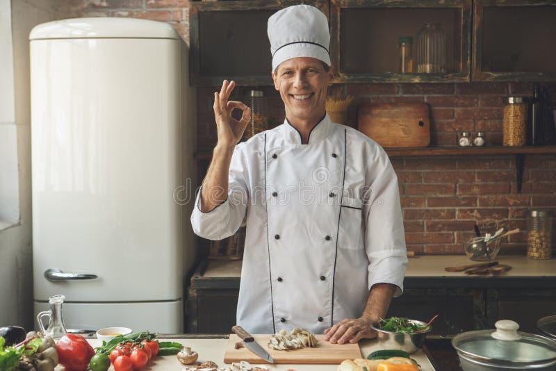 Ώριμο μαγειρεύοντας γεύμα αρχιμαγείρων ατόμων επαγγελματικό στο εσωτερικό στοκ φωτογραφίες με δικαίωμα ελεύθερης χρήσης