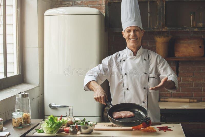 Ώριμο μαγειρεύοντας γεύμα αρχιμαγείρων ατόμων επαγγελματικό στο εσωτερικό στοκ φωτογραφίες
