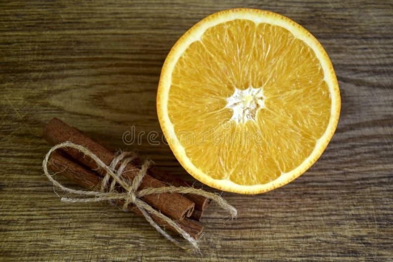 Ώριμο πορτοκάλι, ραβδιά κανέλας στην ξύλινη επιφάνεια στοκ εικόνες