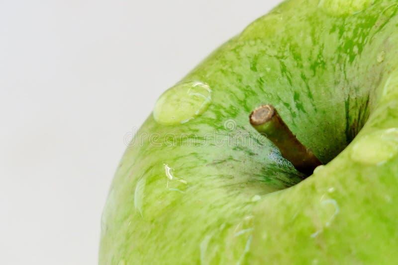 Ώριμο πράσινο μήλο σε ένα άσπρο υπόβαθρο με τις πτώσεις του νερού μετά από τη βροχή στοκ φωτογραφία με δικαίωμα ελεύθερης χρήσης