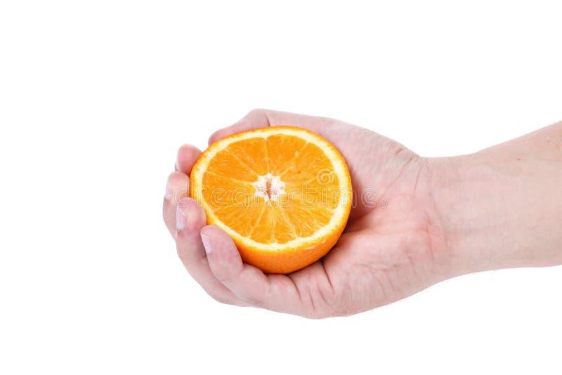 Ώριμο juicy πορτοκάλι συμπιέσεων χεριών. στοκ εικόνα