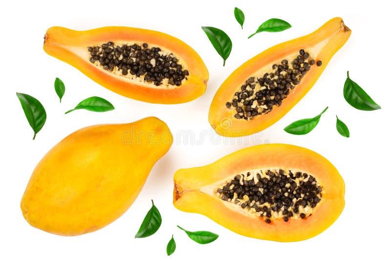 Ώριμο papaya και κατά το ήμισυ απομονωμένος σε ένα άσπρο υπόβαθρο που διακοσμείται με τα πράσινα φύλλα Τοπ όψη Επίπεδος βάλτε στοκ εικόνα