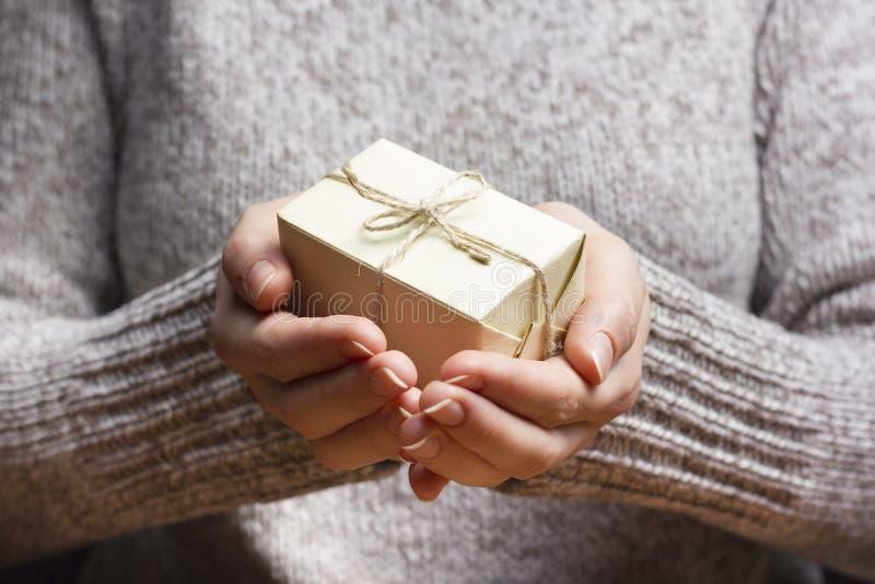 δώρο παρόν Κλείστε επάνω των θηλυκών χεριών κρατώντας το μικρό δώρο στοκ φωτογραφίες