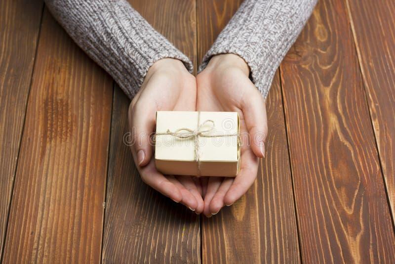 δώρο παρόν Κλείστε επάνω των θηλυκών χεριών κρατώντας το μικρό δώρο στοκ φωτογραφία με δικαίωμα ελεύθερης χρήσης