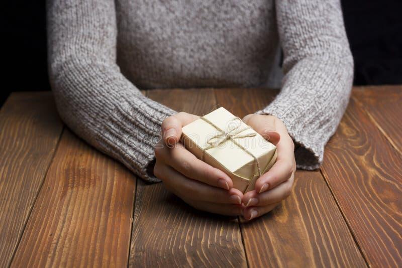 δώρο παρόν Κλείστε επάνω των θηλυκών χεριών κρατώντας το μικρό δώρο στοκ φωτογραφίες με δικαίωμα ελεύθερης χρήσης