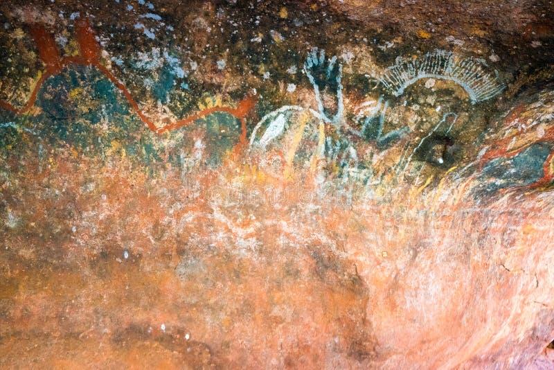 Аборигенная картина пещеры внутри mutitjulu пещеры или kulpi семьи на утесе Ayers в захолустье Австралии стоковое изображение