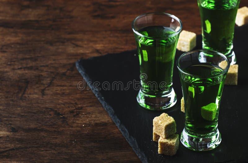 Абсент - сильный алкогольный напиток, зеленая горькая тинктура полыни в стеклах на старом деревянном столе, месте для текста стоковая фотография