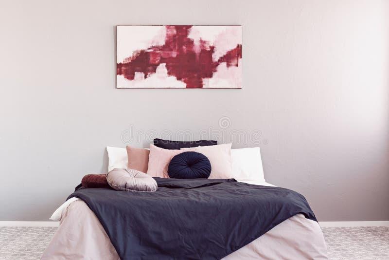Абстрактная амаранта и пастельно-розовая живопись над кроватью размера 'king size' стоковое фото rf
