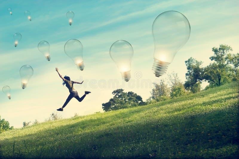 Абстрактная женщина бежать и скача для заразительной электрической лампочки на поле зеленой травы и цветка стоковая фотография