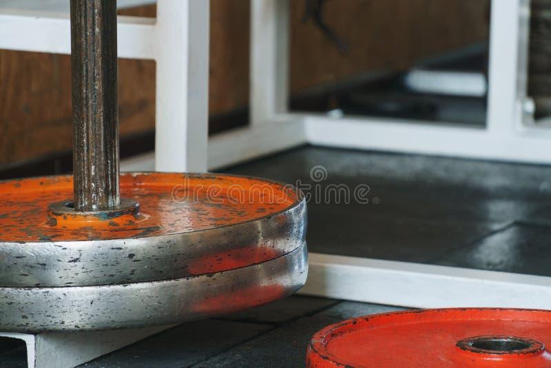 Абстрактная закоренелая предпосылка темы спортзала с ярким апельсином покрасила chapped старые плиты веса помещенный на стойке и  стоковое фото rf