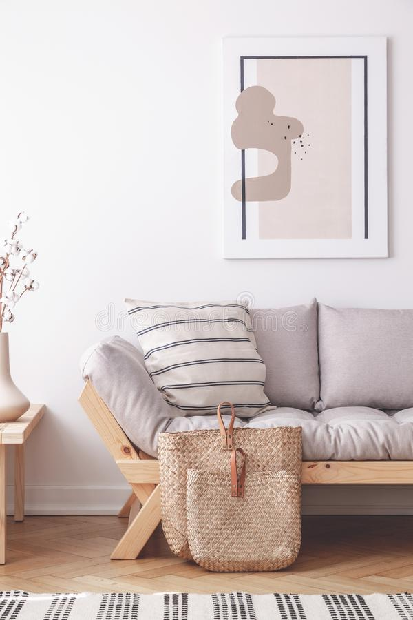 Абстрактная картина на стене естественной бежевой живущей комнаты с серым settee в lagom воодушевила внутреннее стоковые изображения rf