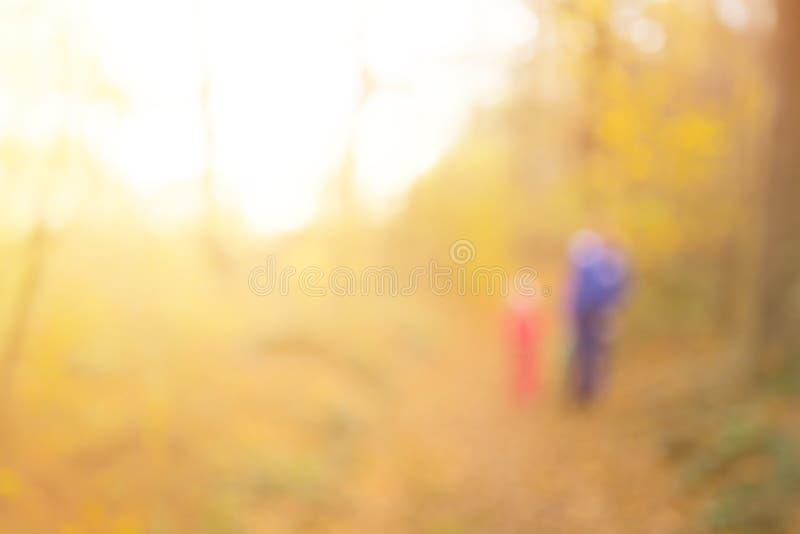 Абстрактная несосредоточенная и мягкая предпосылка для дизайна Мама с младенцем на прогулке Волшебный лес осени с методом нерезко стоковое изображение